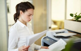 A businesswoman stands next to one of her office's copiers reviewing printed pieces of paper