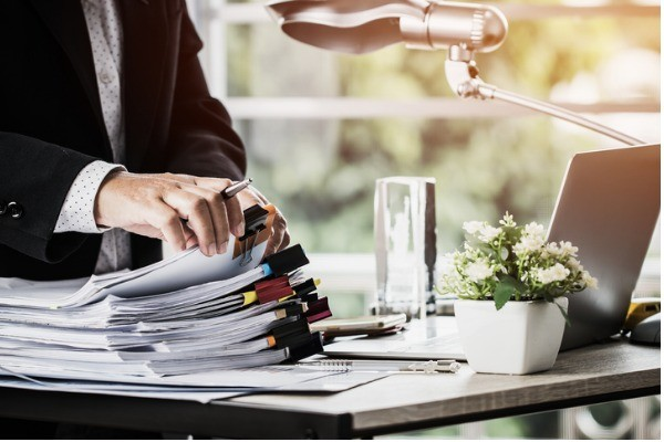 businessman hands holding pen for working in stacks of paper files picture id1068584492 1 - Workflow Solutions