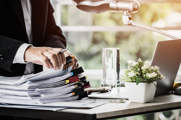 businessman hands holding pen for working in stacks of paper files picture id1068584492 4 - Document Management